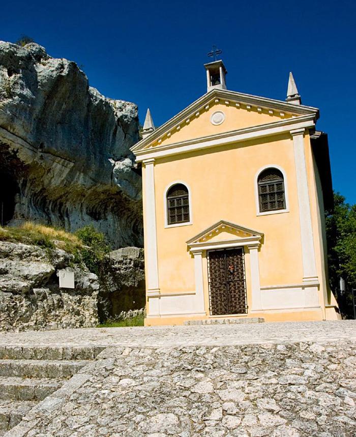 La chiesetta di San Donato oggi, restaurata. Sulla sinistra si vede l'apertura d'ingresso ai covoli, un tempo antico luogo di ritiro monastico, e durante la Prima Guerra riparo pe le truppe qui stanziate.